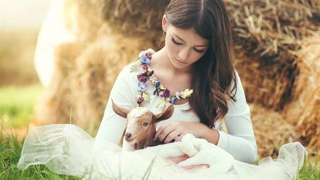 Девушка в цветочном ожерелье с козлёнком на руках
