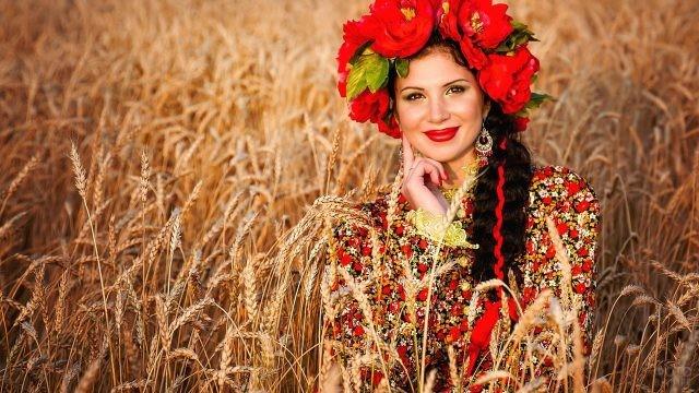 Девушка в венке из красных цветов в пшенице