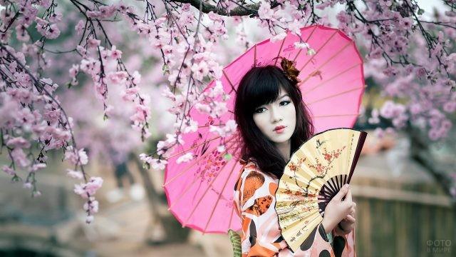 Японка с веером и зонтом у сакуры