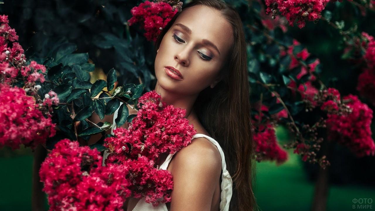 Красивая девушка среди цветов смотрит вниз