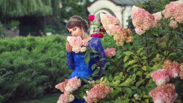 Милая девушка в цветочном саду