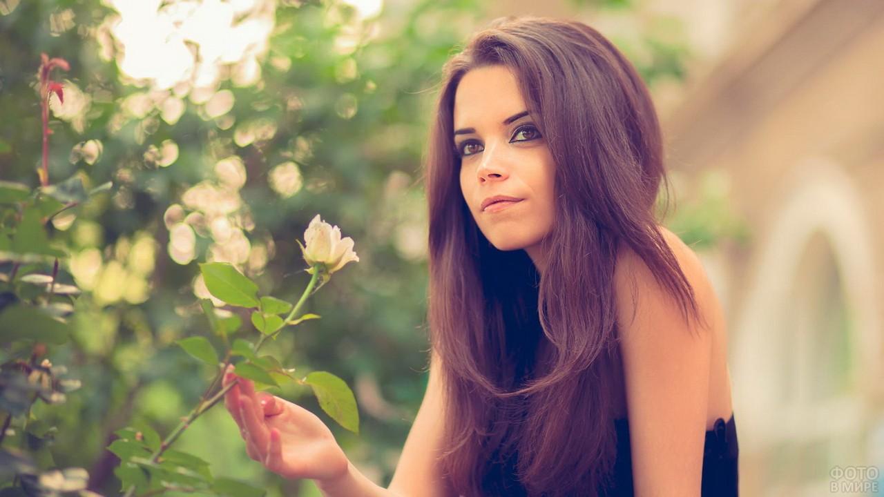Романтичная девушка задумалась возле цветов