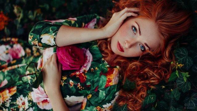 Рыжая девушка лежит с красной розой