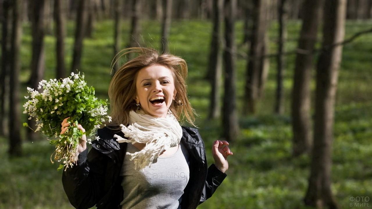 Счастливая девушка бежит по парку с букетом в руке