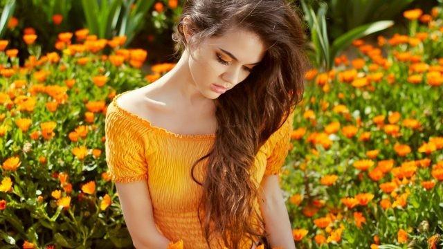 Шатенка в оранжевом платье на фоне календулы