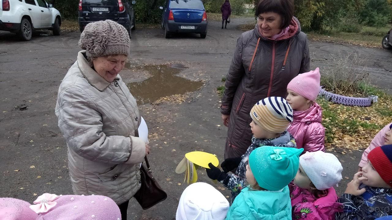 Дети с воспитательницей вышли на улицу поздравить пенсионеров
