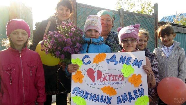 Девочки-школьницы с плакатом и цветами поздравляют учительницу-пенсионерку