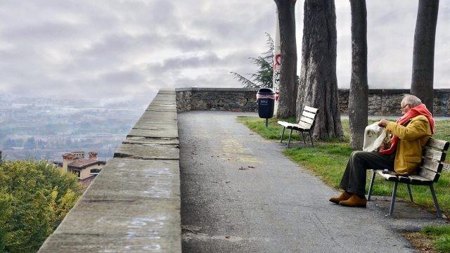 Одинокий пенсионер в ярком шарфе на смотровой площадке в осеннем парке