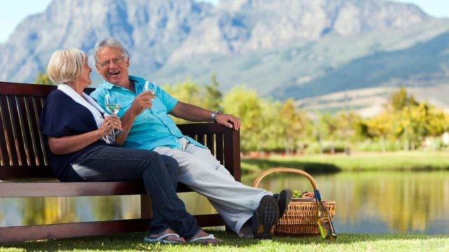 Пара пенсионеров на пикнике у горного озера
