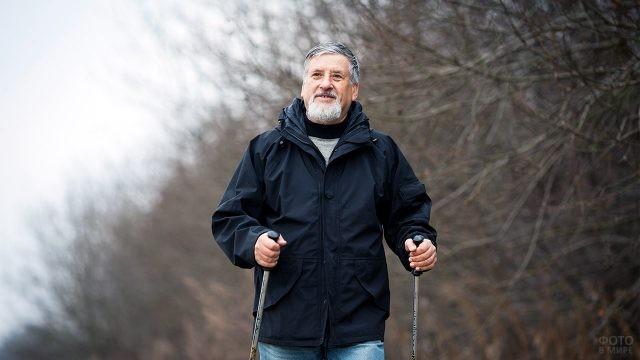 Пенсионер во время занятий скандинавской ходьбой