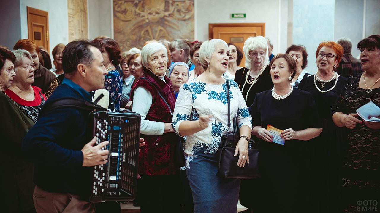 Пенсионерки поют под баян в фойе театра перед началом праздничного концерта