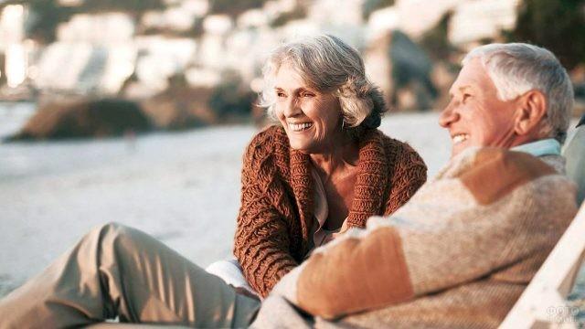 Пенсионеры на закате дня на осеннем пляже