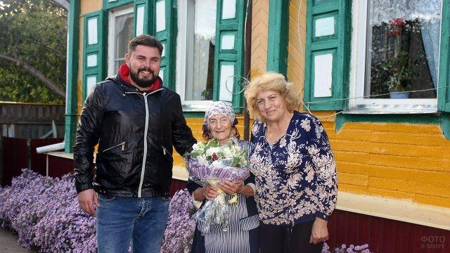 Профсоюзные работники поздравляют коллегу-пенсионерку во дворе её дома