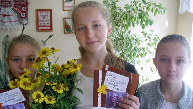 Школьницы с открытками и цветами для учителей-пенсионеров своей школы