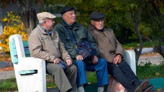 Трое товарищей-пенсионеров на лавочке в осеннем парке