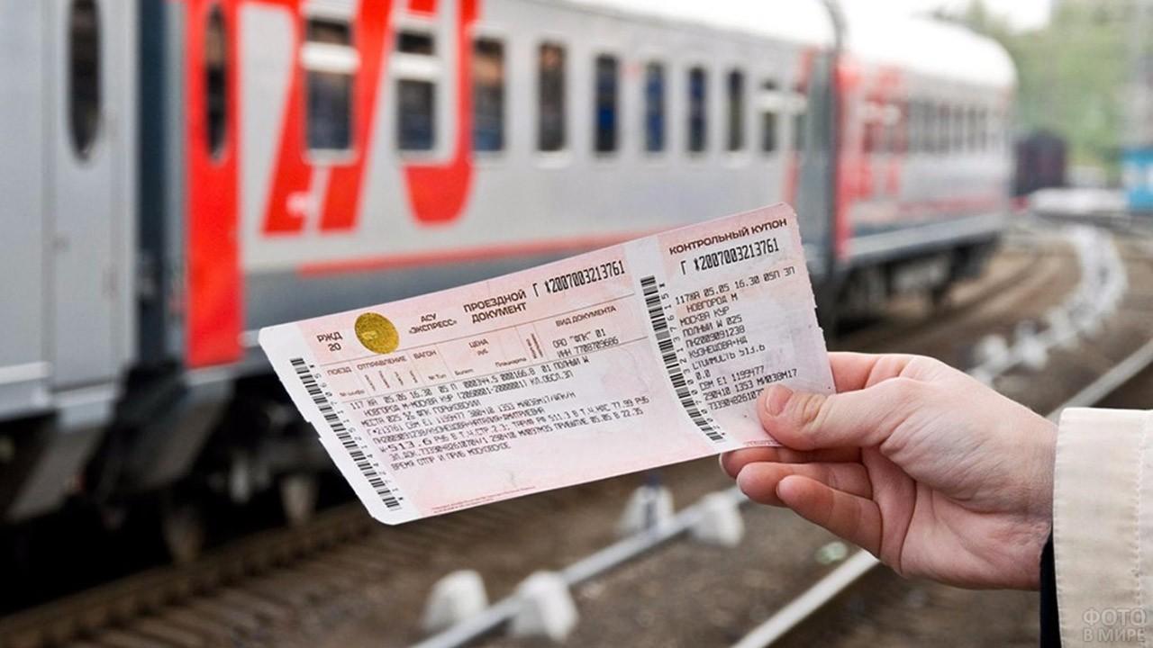 Билет на поезд в руке на фоне железнодорожного состава