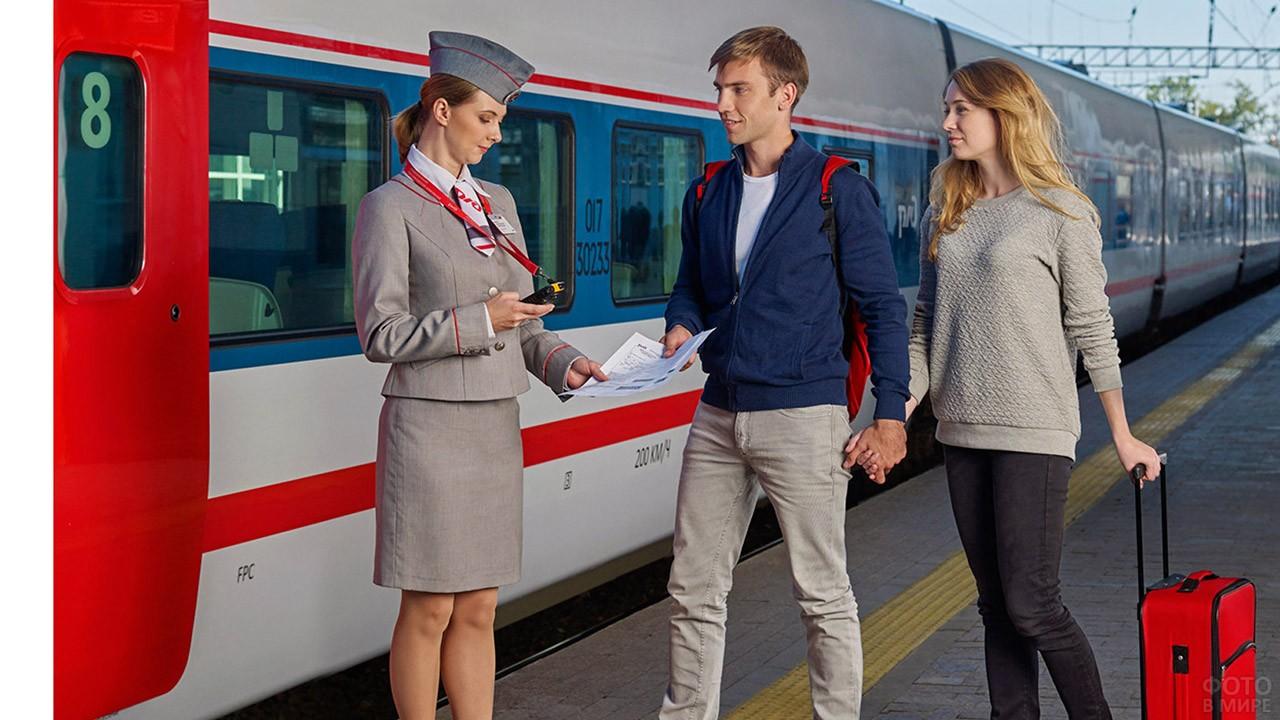 Парочка путешественников и проводница у вагона поезда
