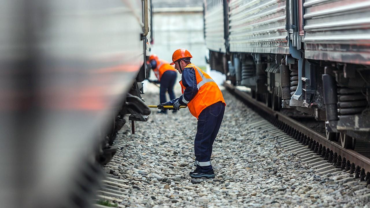 Рабочие-железнодорожники осматривают состав на станции