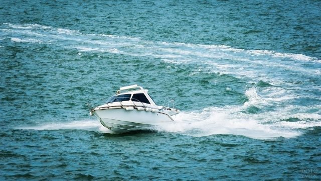 Белый катер красиво поворачивает на волнах
