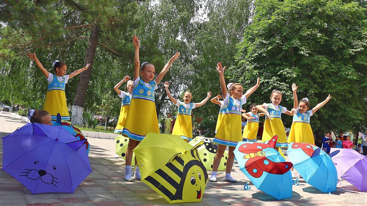 Девочки с зонтиками танцуют на празднике в парке
