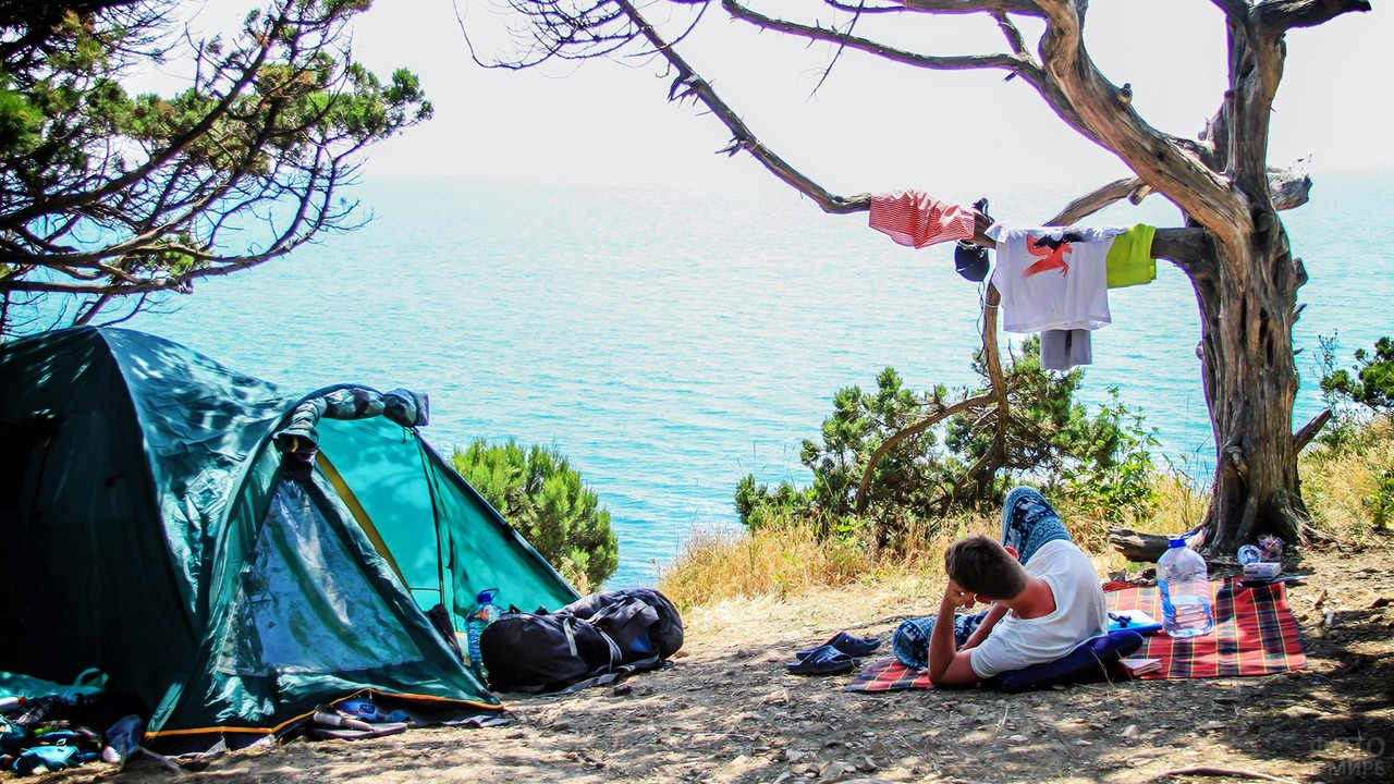 Эко-турист отдыхает в тени у палатки с видом на море