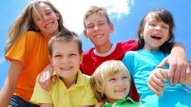 Пятеро улыбающихся малышей на фоне летнего неба