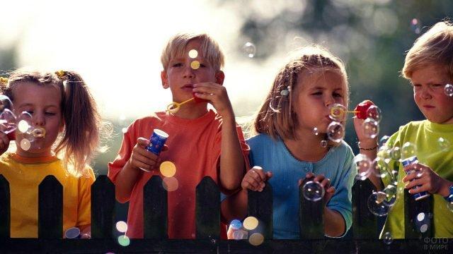 Ребятишки пускают мыльные пузыри в летний день