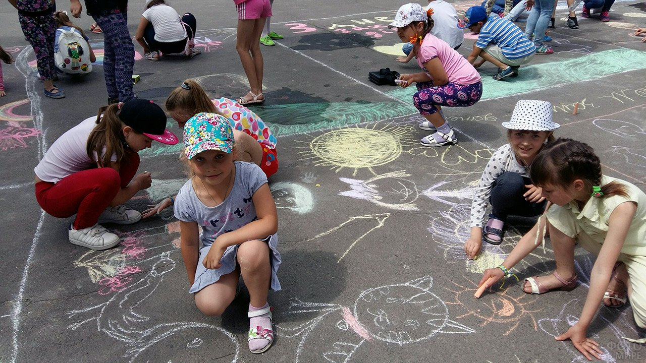 Ребятишки участвуют в конкурсе рисунков на асфальте в День защиты детей