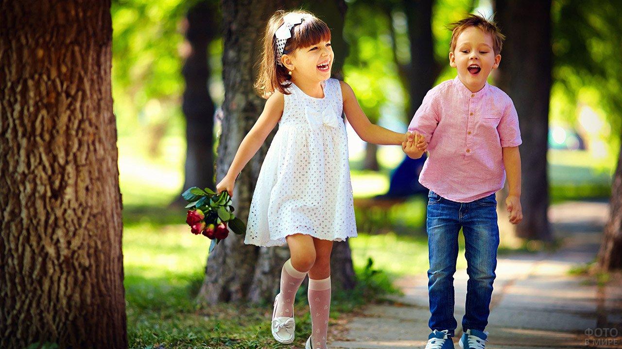 Счастливые мальчик и девочка бегут по дорожке летнего парка