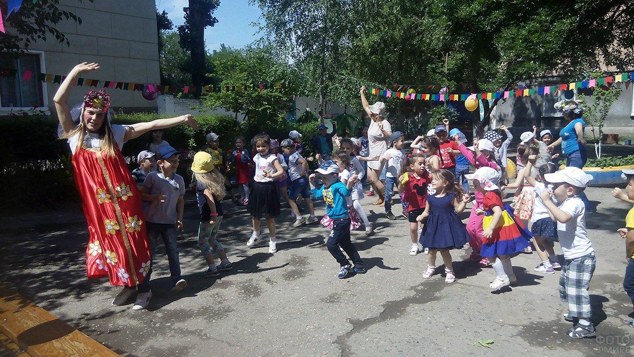 Танцующие с воспитательницами дети в День защиты детей в Моздоке