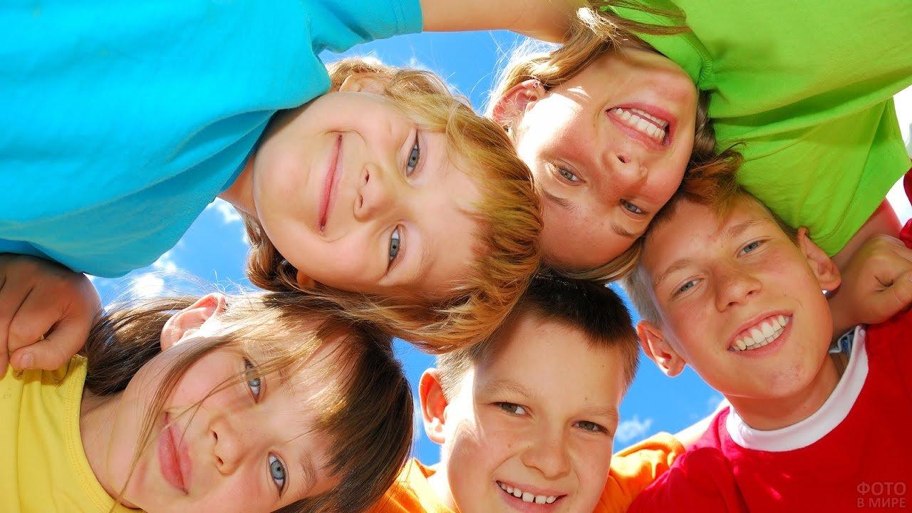 Улыбающиеся дети вкруг смотрят сверху