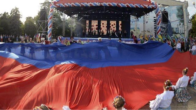 Артисты в народных костюма разных национальностей держат триколор в День России