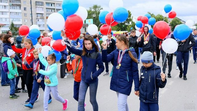Дети с шариками цветов российского флага на улице города 12 июня