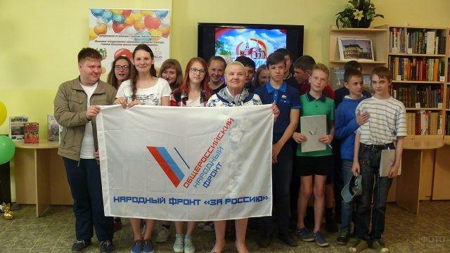 Дети в школьной библиотеке в День России с флагом политической организации