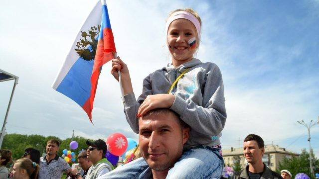Девочка на плечах у отца с триколорами в День России