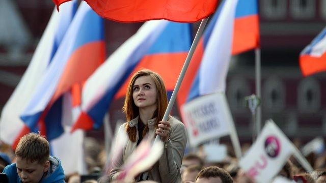 Красивая девушка под флагом России в толпе празднующих 12 июня