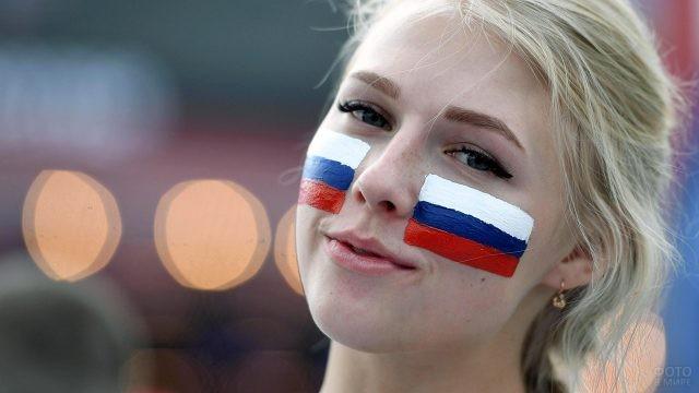Красивая юная блондинка с нарисованными триколорами на фоне городских огоньков