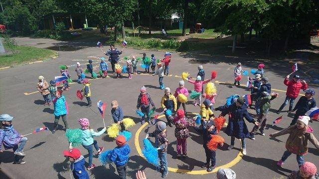 Малыши во дворе детского сада танцуют в День России
