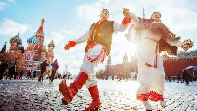 Молодая пара в народных костюмах на Красной площади в солнечный День России