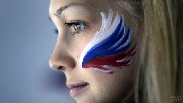 Профиль блондинки с нарисованным на щеке крылом птицы в цветах флага России