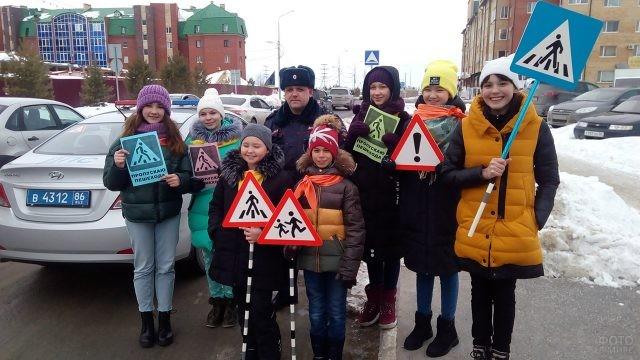Дети-волонтёры и сотрудник ГИБДД со знаками в руках