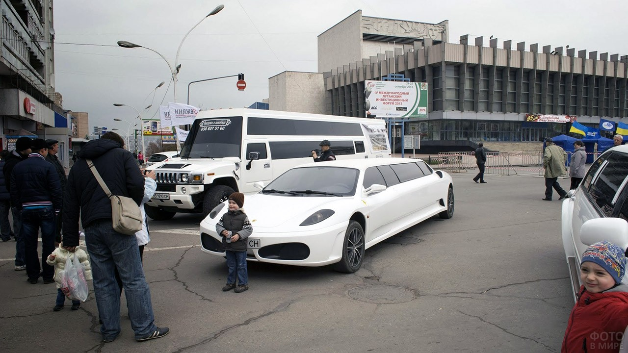 Малыши фотографируются у лимузинов на городском празднике