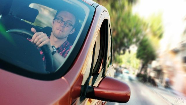 Мужчина в очках за рулём красного автомобиля
