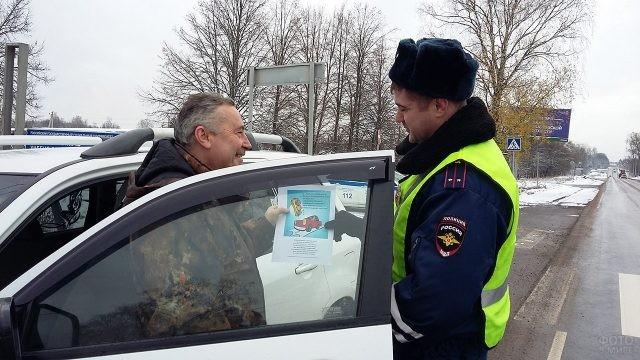 Сотрудник ГИБДД вручает водителю открытку
