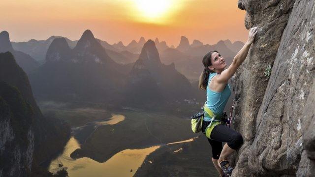 Альпинистка поднимается по скале