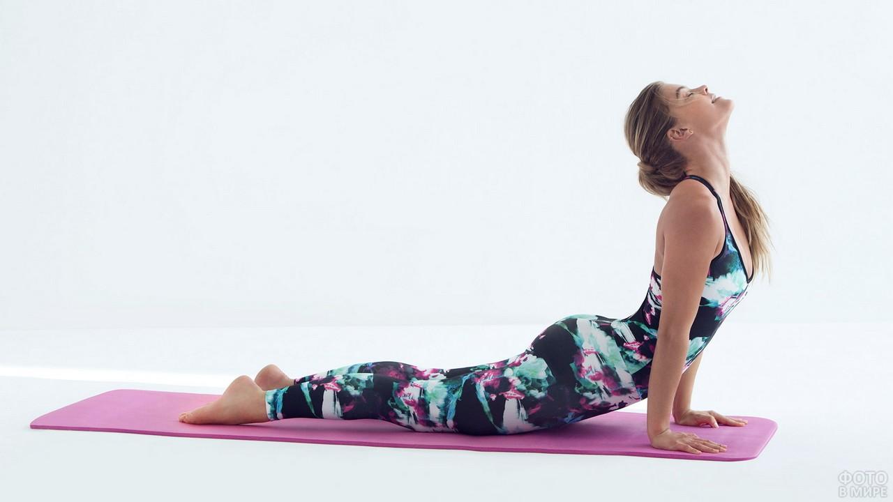 Девушка делает упражнение на розовом коврике