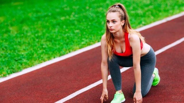 Девушка на беговой дистанции ждёт старта