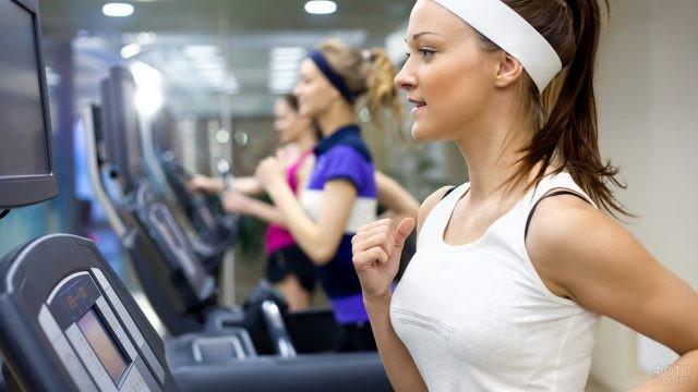 Девушка на беговой дорожке в спортзале