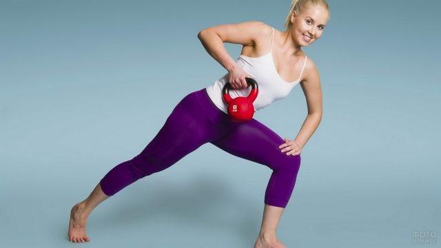 Девушка поднимает спортивную гирю
