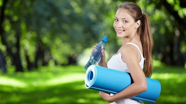 Девушка с бутылкой воды и карематом
